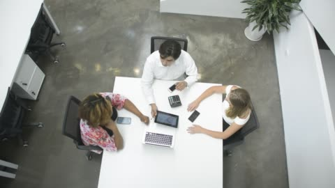 high angle view of business people in discussion in office - three people stock videos & royalty-free footage