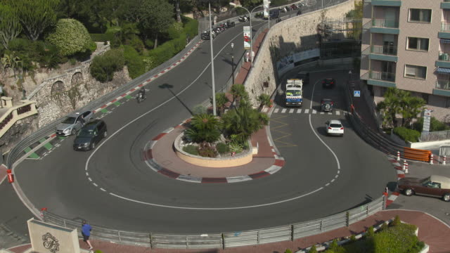 high angle view of busses going round the famous hairpin bend in monte-carlo with grand prix markings on the side of the road - monaco stock videos and b-roll footage