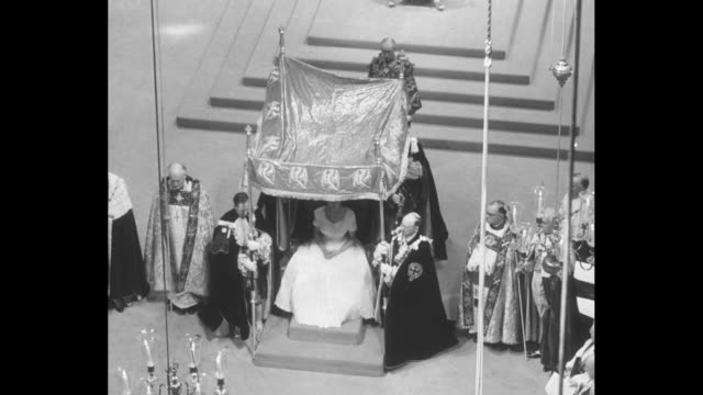 vs high angle view of canopy being moved into position over queen elizabeth ii prior to her anointing / st edward's crown is raised over her head... - throne stock videos & royalty-free footage