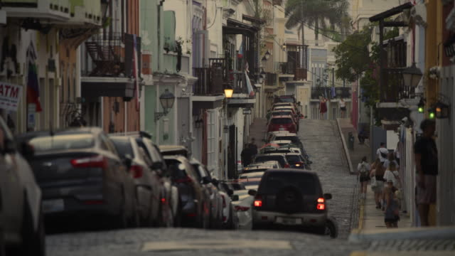 high angle view of cars and people on cobblestone city street / san juan, puerto rico - cobblestone stock videos & royalty-free footage