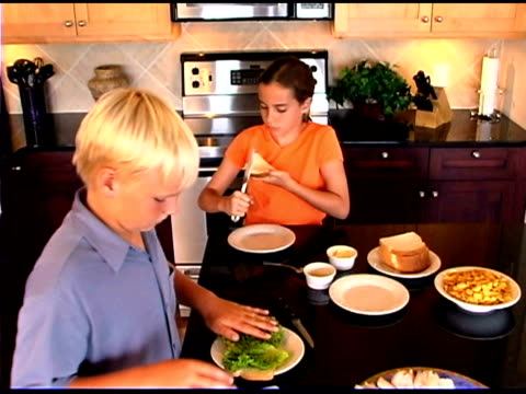 high angle view of children preparing food in kitchen - making a sandwich stock videos and b-roll footage