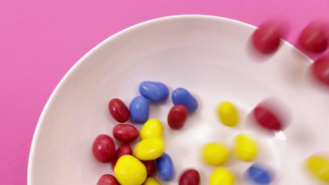 vídeos y material grabado en eventos de stock de high angle view of colorful candies falling in a bowl - dulces
