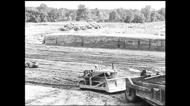 vidéos et rushes de high angle view of construction site with houses nearby and cars parked by the road; partially completed building next to dirt road; tractors plowing... - 1940 1949