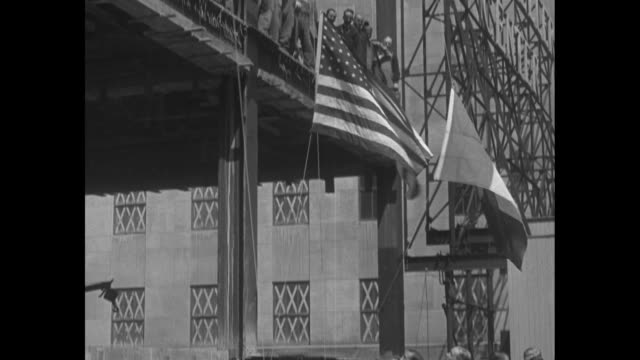 high angle view of construction with fifth avenue below a look down at girders of building and pan up to topmost girder decorated with american... - ネルソン a ロッカフェラー点の映像素材/bロール