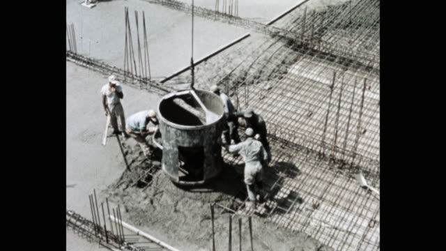 high angle view of construction workers pouring concrete at construction site - cement stock videos & royalty-free footage