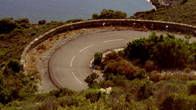 High angle view of convertible on winding mountain road / sunlight reflecting off water below / Corsica