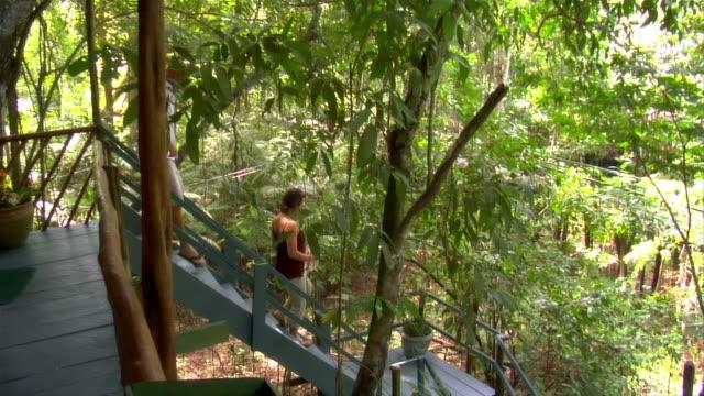 vídeos y material grabado en eventos de stock de high angle view of couple leaving eco-lodge and walking downstairs / the amazon, brazil - brasil
