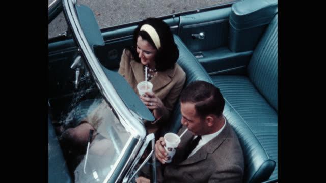 vídeos de stock, filmes e b-roll de high angle view of couple sipping drinks from straws while sitting in convertible - copo descartável