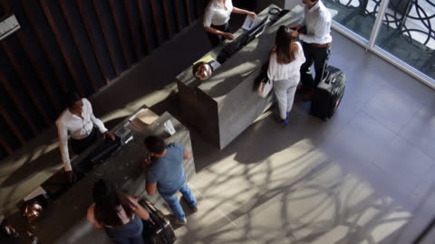 high angle view of couples checking into hotel at the front desk - receptionist stock videos & royalty-free footage