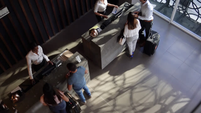 vídeos de stock e filmes b-roll de high angle view of couples checking into hotel at the front desk - employee