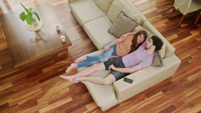 high angle view of cozy couple on sofa in modern home - close to stock videos & royalty-free footage