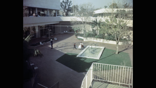 high angle view of family relaxing outdoors at the beverly hilton hotel, los angeles, california, usa - the beverly hilton hotel stock videos & royalty-free footage