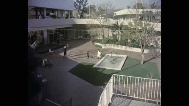 high angle view of family relaxing outdoors at the beverly hilton hotel, beverly hills, california, usa - the beverly hilton hotel stock videos & royalty-free footage