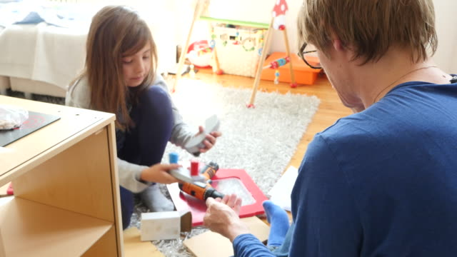 High angle view of father and daughter preparing toy kitchen
