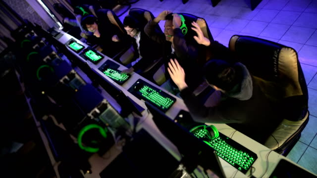 vídeos de stock e filmes b-roll de high angle view of gamers winning in esport match in internet game cafe - competição