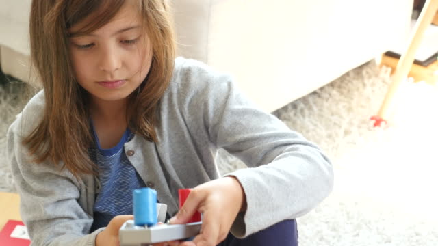 High angle view of girl fixing toy faucet at home
