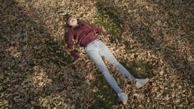 high angle view of girl laying in autumn leaves making angel / cedar hills, utah, united states - 仰向きに寝る点の映像素材/bロール