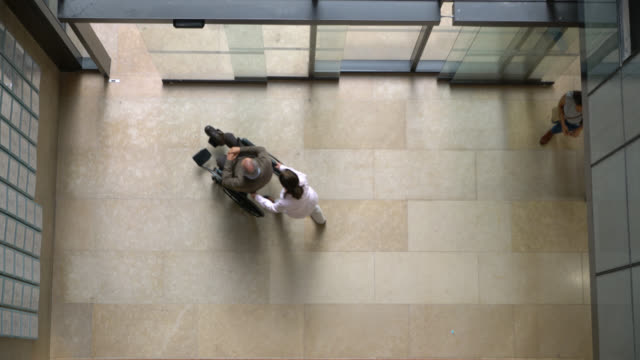 high angle view of healthcare professionals and people walking in and out of hospital - building entrance stock videos & royalty-free footage