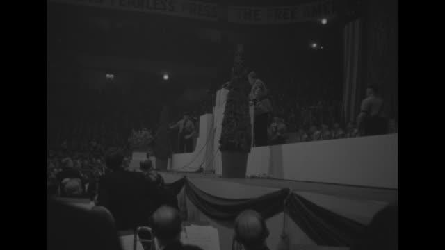 high angle view of huge audience at madison square garden for the german-american bund rally; portrait of george washington serves as backdrop on... - the bund stock videos & royalty-free footage