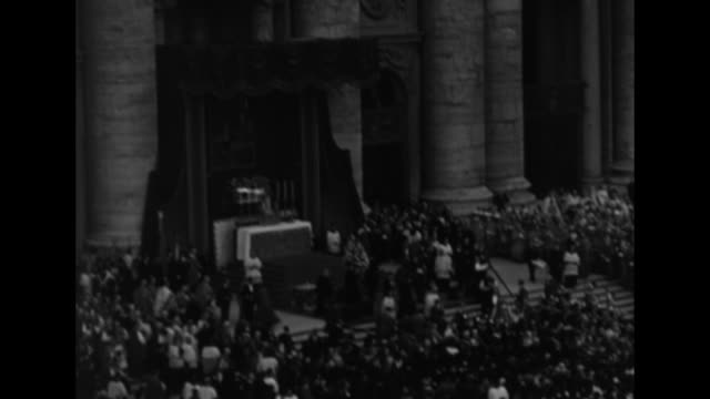 High angle view of huge crowd in St Peter's Square / outdoor altar with banner of Pius X / procession with Pius XII atop gestatorial chair in crowd /...