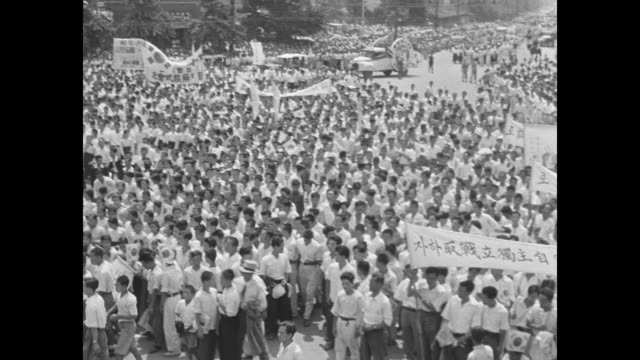 high angle view of hundreds of south korean people wearing white and holding banners / vs military governor general john r hodge wears sunglasses and... - korea stock videos & royalty-free footage