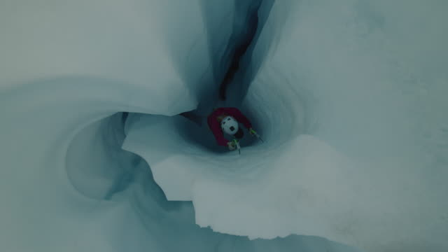 High angle view of ice climber ascending narrow crevice on glacier using hooks / Palmer, Alaska, United States