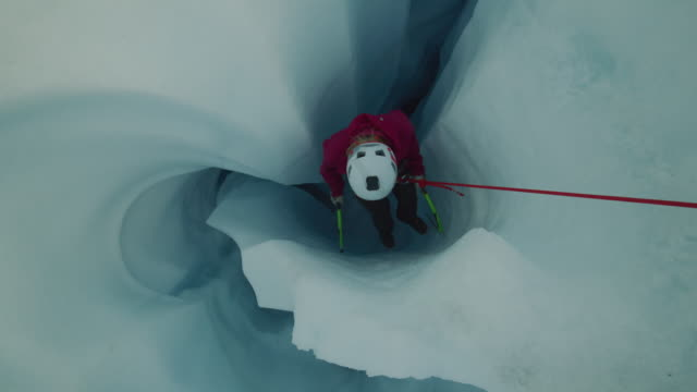 high angle view of ice climber descending narrow crevice on glacier using rope / palmer, alaska, united states - crevice stock videos & royalty-free footage