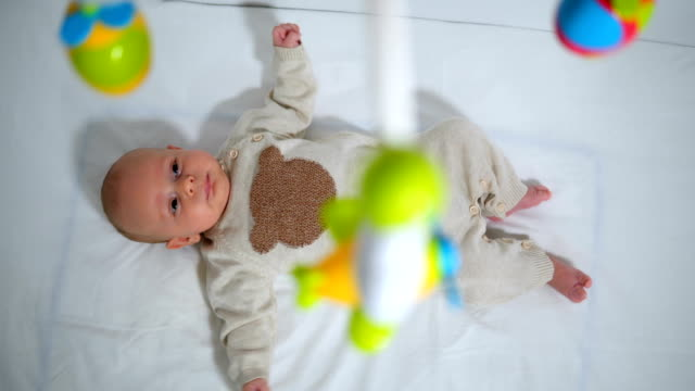 high angle view of innocent baby boy looking at toys hanging in crib - crib stock videos & royalty-free footage
