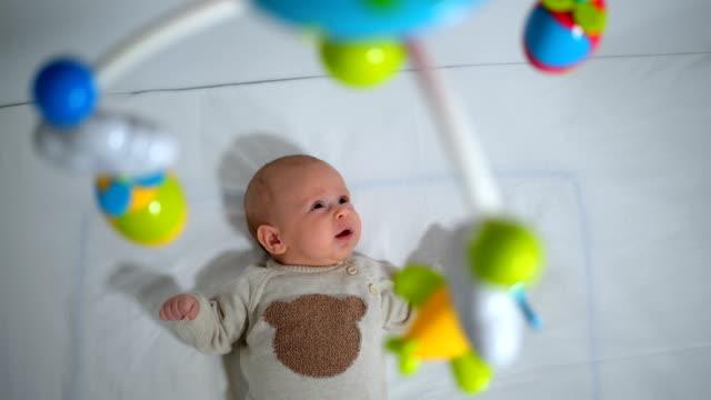 無邪気な男の赤ちゃんのベビーベッドにぶら下がっているおもちゃを見てハイアングル - おもちゃ点の映像素材/bロール