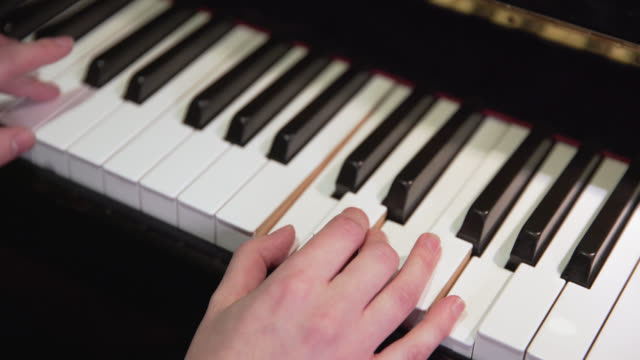 high angle view of keys being played on a piano - pianist stock-videos und b-roll-filmmaterial