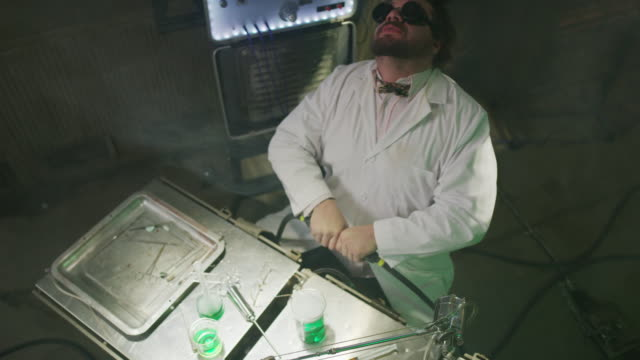 stockvideo's en b-roll-footage met high angle view of mad scientist connecting electrical cords and shocking himself / cedar hills, utah, united states - wetenschapper