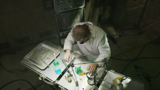 High angle view of mad scientist drinking liquid in laboratory then choking / Cedar Hills, Utah, United States