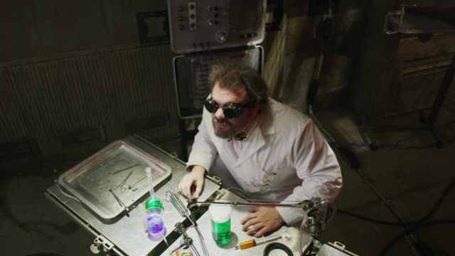 high angle view of mad scientist drinking liquid in laboratory then laughing / cedar hills, utah, united states - schutzbrille stock-videos und b-roll-filmmaterial