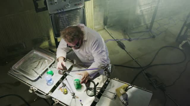 high angle view of mad scientist injecting liquid into beaker with syringe / cedar hills, utah, united states - wissenschaftliches experiment stock-videos und b-roll-filmmaterial