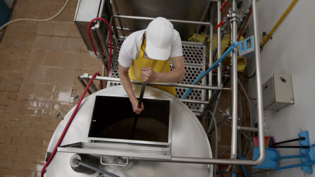 high angle view of man cleaning a distillery tank at a brewery factory - vat stock videos & royalty-free footage