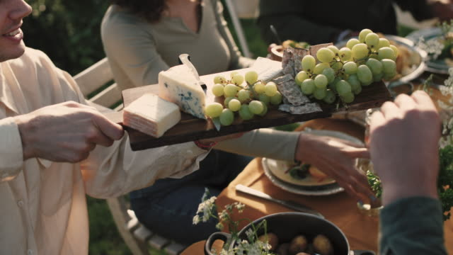 High angle view of man giving cutting board with grapes and cheese to friends at garden party
