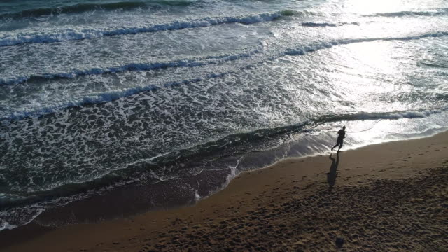 High angle view of man jogging on the beach