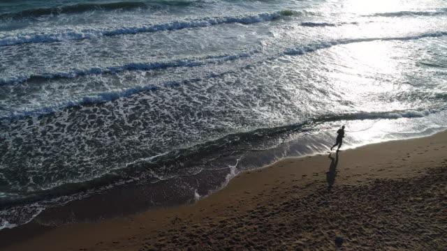 vidéos et rushes de vue d'angle élevé de l'homme, faire du jogging sur la plage - jogging
