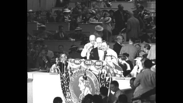 high angle view of man speaking at podium of 1936 democratic national convention;, abc, nbc and mbs logos on microphones / man introduces judge john... - politik und regierung stock-videos und b-roll-filmmaterial