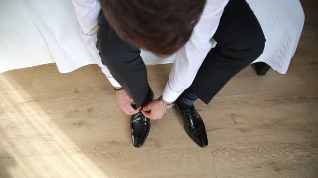 high angle view of man tying shoe laces - shirt stock videos & royalty-free footage