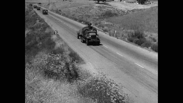 high angle view of military land vehicles driving on country road - medium group of people stock videos & royalty-free footage