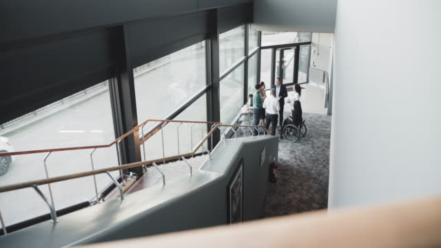 high angle view of multi-ethnic business colleagues discussing in corridor by staircase at coworking office - employee engagement stock videos & royalty-free footage