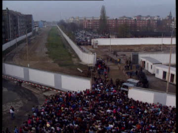 stockvideo's en b-roll-footage met high angle view of new opening in berlin wall now completed as huge crowds of east germans start to go through into west berlin. east german army... - omwalling