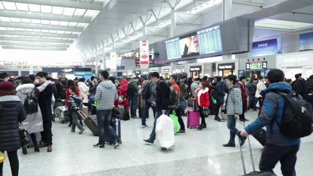 High angle view of passengers standing at ticket counters to purchase train tickets at the Shanghai Hongqiao Railway Station in Shanghai China on...