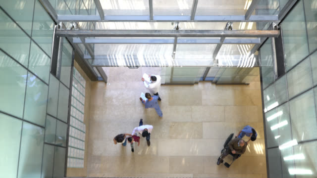 high angle view of people and healthcare professionals walking in and out of the hospital - building entrance stock videos & royalty-free footage