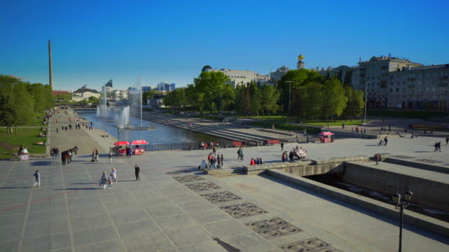 high angle view of people walking on footpath by fountain at park during sunny day - yekaterinburg, russia - large group of animals点の映像素材/bロール