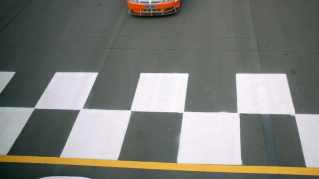 An orange car barely beats two other cars across the finish line at Pocono Raceway.