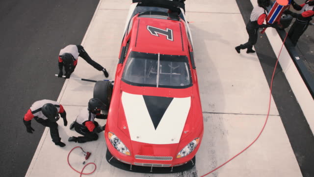 High angle view of pit crew hard at work jacking stock car, refueling, and changing tires.
