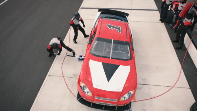 SLO MO. High angle view of pit crew jacking, refueling, and changing tires on stock car.