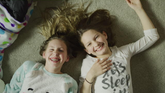 high angle view of portrait of laughing girls at sleep over laying on floor / cedar hills, utah, united states - slumber party stock videos and b-roll footage